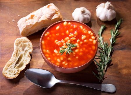 frijoles: tazón de sopa de frijoles con romero en la mesa de madera, vista desde arriba
