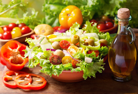 vegetable salad: bowl of fresh vegetable salad on wooden table
