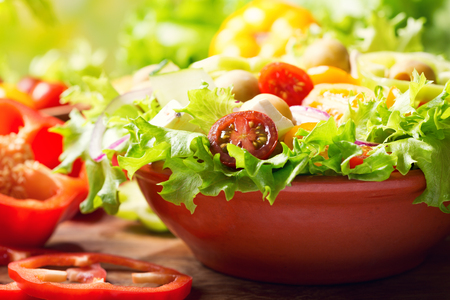bowl of fresh vegetable salad on wooden table