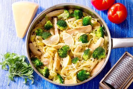 pasta sauce: pan of pasta with chicken and broccoli on wooden table, top view Stock Photo