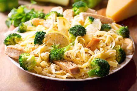 garnish: plate of pasta with chicken and broccoli on wooden table