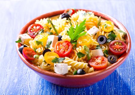 kom pasta salade met groenten op houten tafel