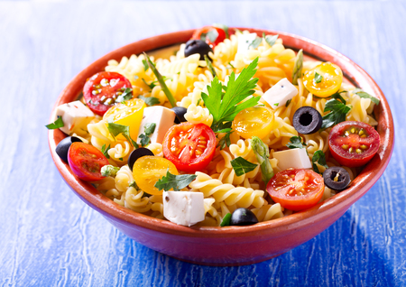 bowl of pasta salad with vegetables on wooden table
