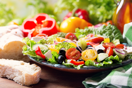 plate of greek salad on wooden table 스톡 콘텐츠