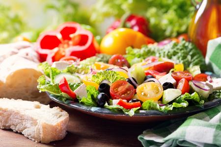 plate of greek salad on wooden table Foto de archivo