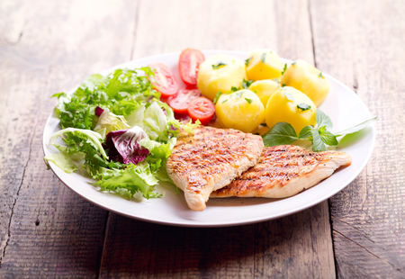 chicken breast: plate of grilled chicken breast with vegetables on wooden table