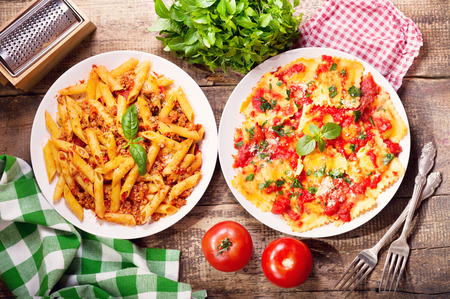 plates of traditional italian food. Pasta bolognese and ravioli with tomato sauce