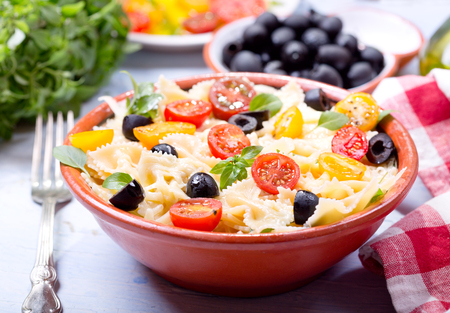 pasta salad: bowl of pasta salad with vegetables on wooden table