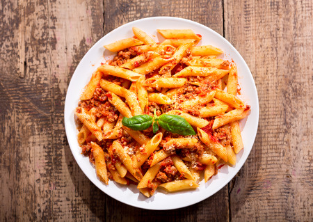 plate of penne pasta bolognese on wooden table 免版税图像 - 49201052