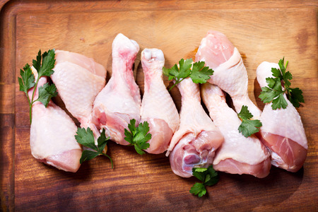 chicken leg: raw chicken legs on wooden board