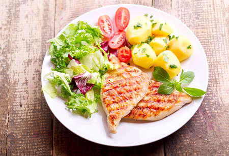 plate of grilled chicken breast with vegetables on wooden table