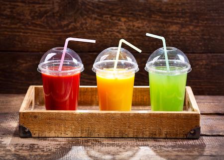 various fresh juices on wooden background Foto de archivo