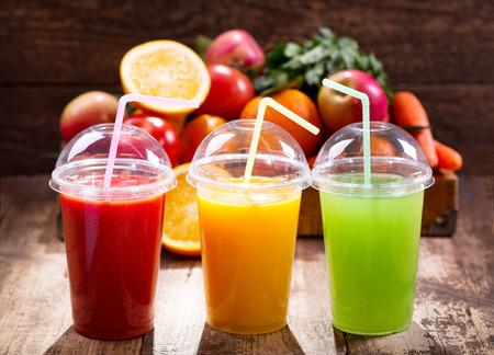 jugo de frutas: Los jugos frescos con frutas y verduras en el fondo de madera