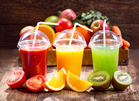 Fresh juices with fruits and vegetables on wooden background