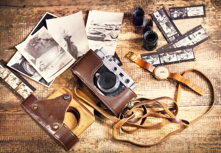 camera: retro camera and old photos on wooden background Stock Photo