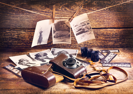 old desk: retro camera and old photos on wooden background Stock Photo