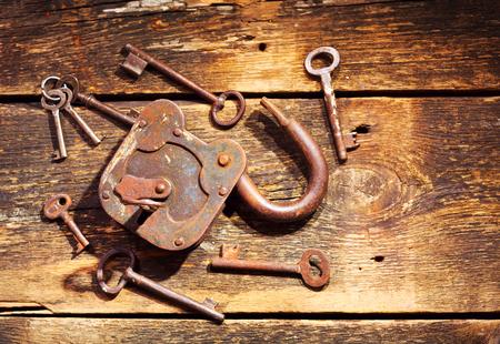oxidado: old rusty lock and keys on wooden table