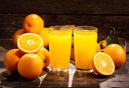 fruits juice: glasses of orange juice with fresh fruits on wooden background