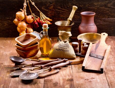 cocina vieja: diversos utensilios de cocina en el fondo de madera rústica