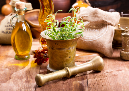 fresh rosemary in a mortar on wooden table Stock Photo