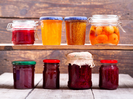 various jars of fruit jam on wooden background Standard-Bild