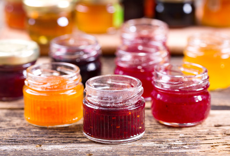 various jars of fruit jam on wooden table Stockfoto