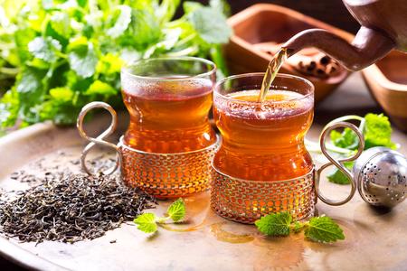Tee aus Teekanne in Glas gießen
