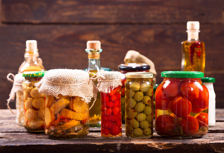 marinated gherkins: various preserved food on wooden background Stock Photo