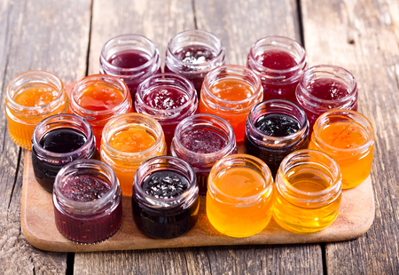 various jars of fruit jam on wooden table Standard-Bild