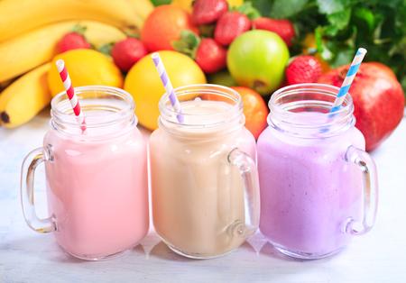 tomando leche: tarros de batido de frutas con pajitas de rayas Foto de archivo