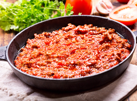 carne picada: meat sauce in a pan on wooden table Foto de archivo