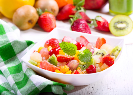 summer fruits: bowl of fruit salad on wooden table