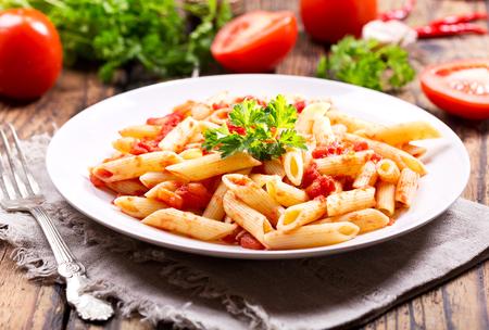 salsa de tomate: plato de pasta con salsa de tomate en la mesa de madera Foto de archivo