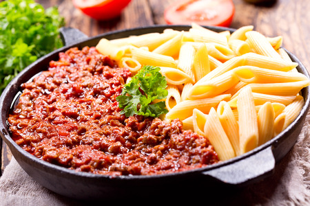 pan: pasta bolognese in a pan on wooden table