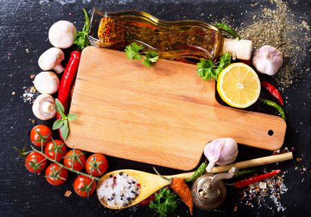 wooden board: empty wooden board  with various products for cooking on dark board Stock Photo