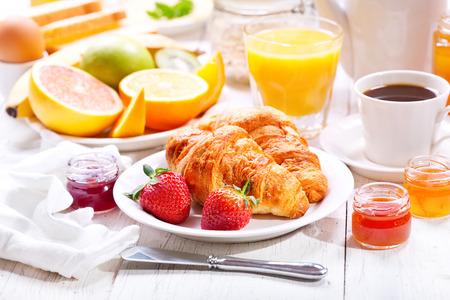 クロワッサン、コーヒー、オレンジ ジュース、トースト、フルーツと朝食用のテーブル