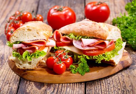 jamon: dos s�ndwiches con jam�n y verduras en la tabla de madera Foto de archivo