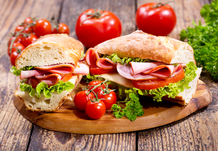 zwei Sandwiches mit Schinken und Gemüse auf Holzbrett Standard-Bild