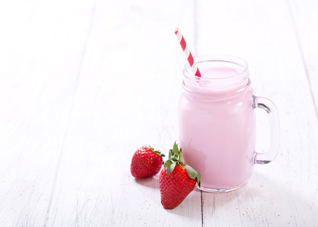a straw: jar of strawberry smoothie on wooden table