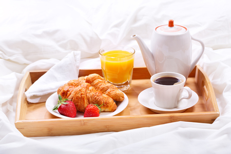 breakfast cup: Breakfast in bed. Tray with cup of coffee and croissants
