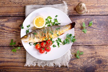 baked: plate of baked sea bass on wooden table