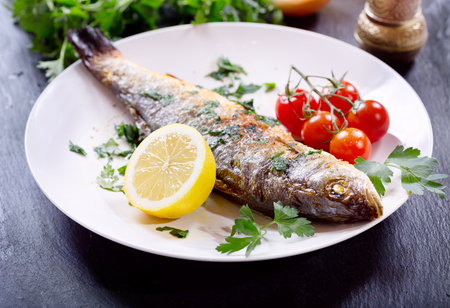 sea bass: plate of baked sea bass on dark background