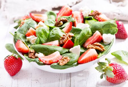 spinach salad: bowl of salad with strawberry, spinach leaves and feta cheese on wooden table Stock Photo