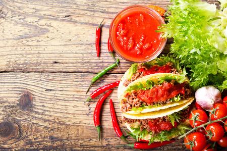 bailar salsa: Los tacos mexicanos con carne y salsa en una mesa de madera, vista desde arriba Foto de archivo