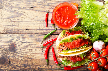 salsa: mexican tacos with meat and salsa on a wooden table, top view