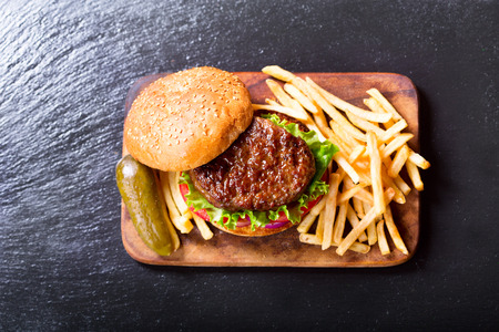 hamburger with vegetables and fries on a wooden board, top view.
