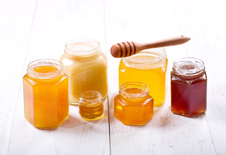 various types of honey in glass jars on a wooden table