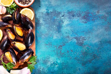 mosselen met peterselie en citroen op een houten bord, bovenaanzicht Stockfoto