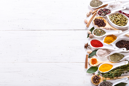 various herbs and spices for cooking on wooden table, top view