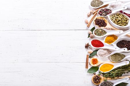 verschiedene Kräuter und Gewürze für das Kochen auf Holztisch, Ansicht von oben